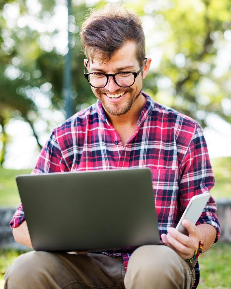 young-man-smartphone-browsing-laptop-concept-PL96PN7.jpg